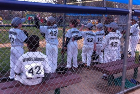 Photo of youth baseball players in dugout watching game